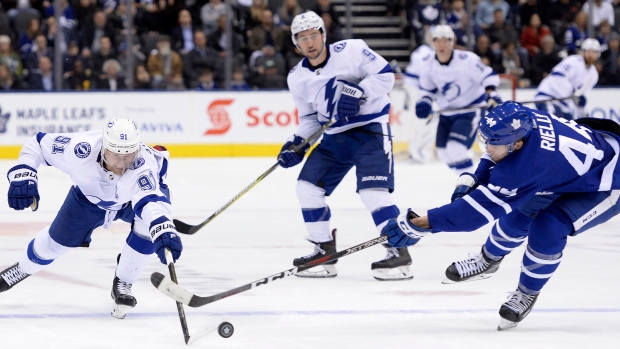 Lightning centre Steven Stamkos and Leafs defenceman Morgan Rielly battle for the puck.