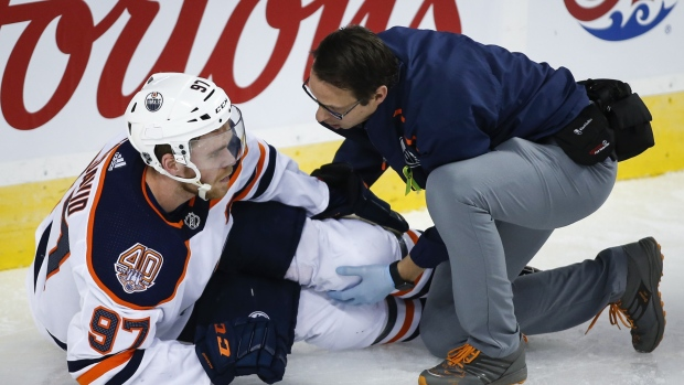 Connor McDavid, left, has his knee tended too after crashing into Calgary Flames goalie Mike Smith