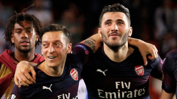 Two men charged following incident at Ozil's home