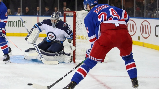 Jets goalie Connor Hellebuyck sets up for a shot by Rangers winger Kaapo Kakko.