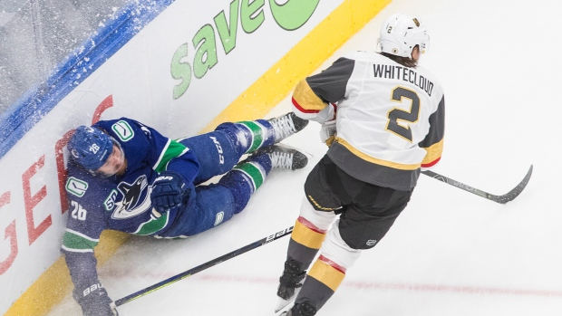 Vegas Golden Knights' Zach Whitecloud and Vancouver Canucks' Antoine Roussel