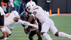 Oklahoma State's Chuba Hubbard tackled by Texas defenders