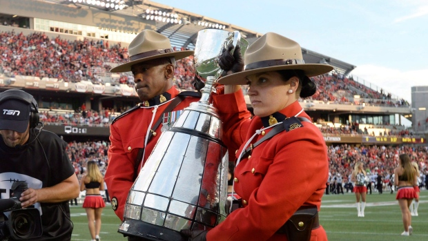 RCMP officers carry the Grey Cup